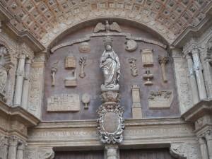 Portal Major de la Seu (1601): la Mare de Déu amb atributs sobre el fons de la Lletania Lauretana: el sol, la lluna, les estrelles, arbres, pous, una casa.